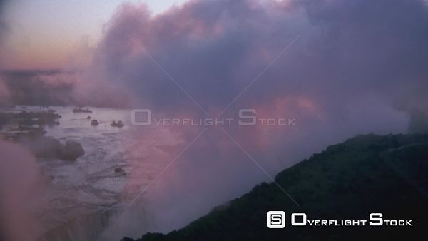 Aerial wide angle shot thick mist obscuring Victoria Falls at sunset sunrise, side view of river flowing towards falls with v...