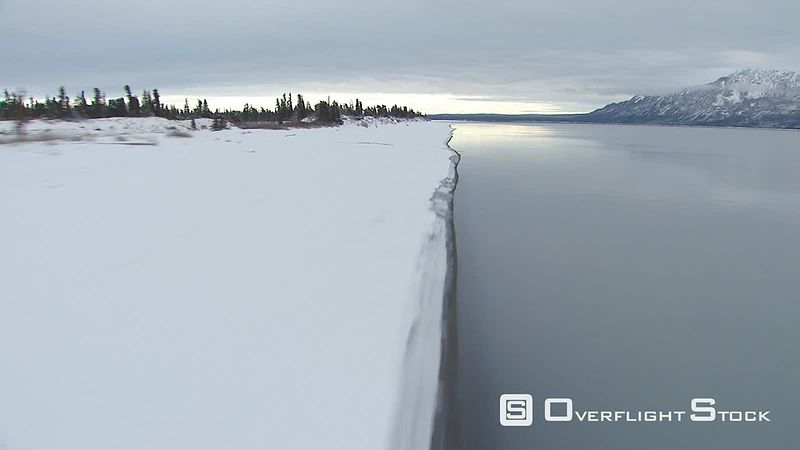 Flying along course of icy river in Alaska