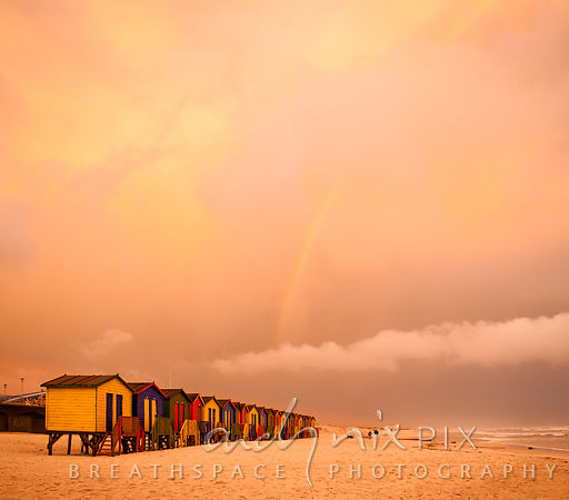 Muizenberg beach huts at sunset with storm clouds and rainbow