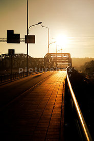 An atmospheric image of the sun setting behind a road bridge.