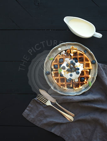 Soft Belgian waffles with blueberries, honey and whipped cream on vintage metal plate over black wooden background, top view