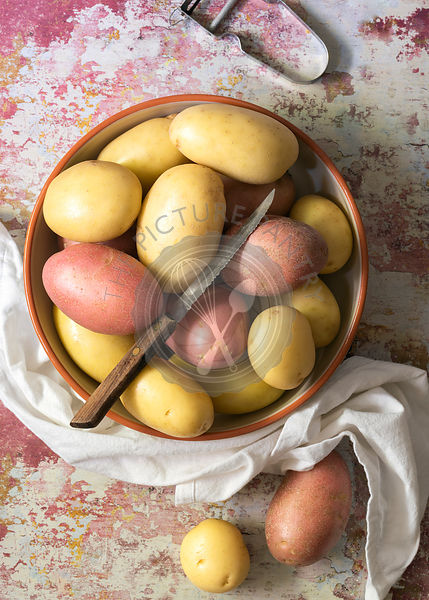 Royale Red and Creme Gold washed potatoes in a bowl with a knife.