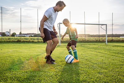 Coach and young football player on football ground at sunset