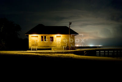 An atmospheric image of a flood lit, wooden jetty leading to a cabin on a palm covered desert island, at night.