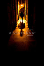 An atmospheric image of the silhouette of a mystery man, standing in an alley at night.