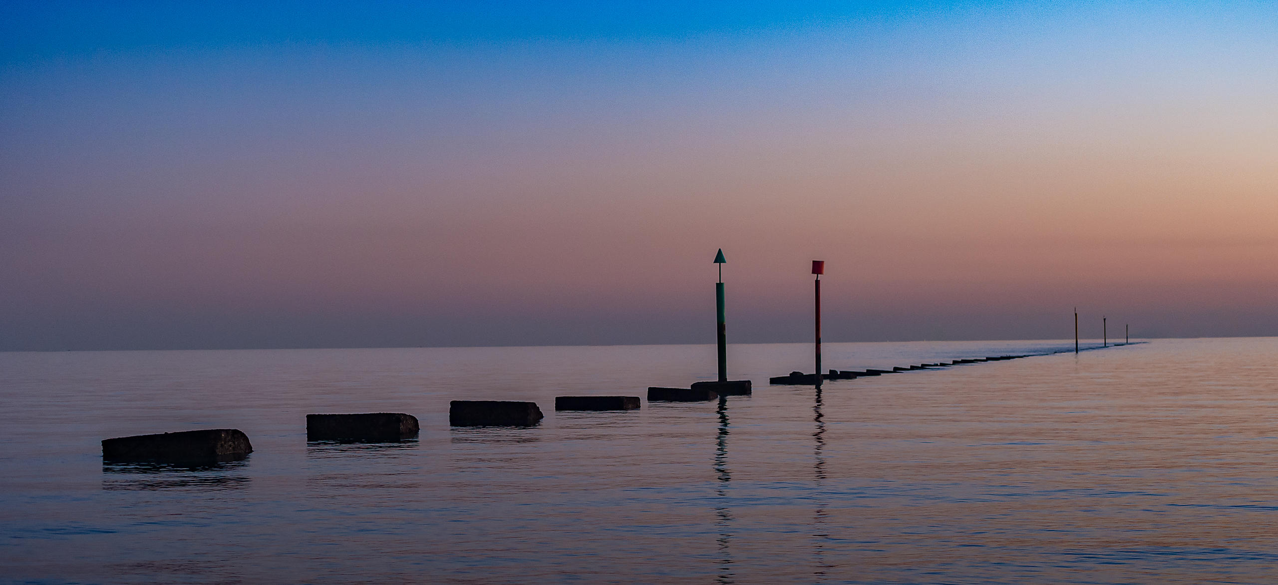 Sea Defences on the Solent at Dusk with Pink Sky and Calm Water