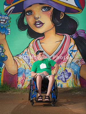 Man in a wheelchair taking in street art