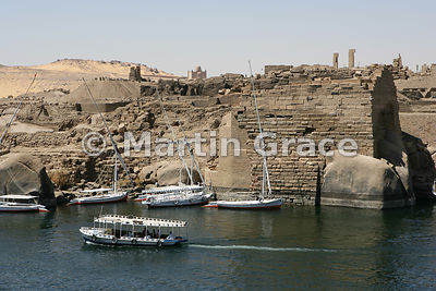 The River Nile at Aswan, Egypt, with tourist boats, the Temple of Khnum on Elephantine Island, and the Aga Khan Mausoleum on ...