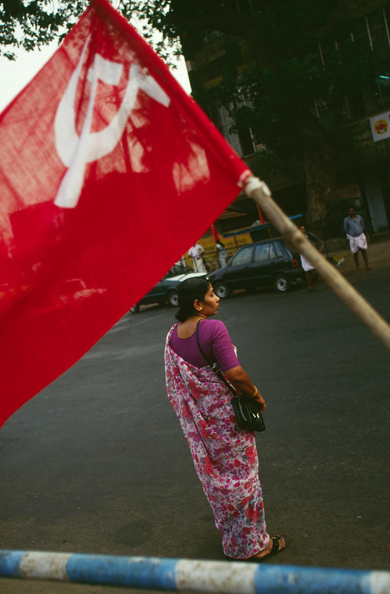 India - Kerala - A woman walks past a Communist flag