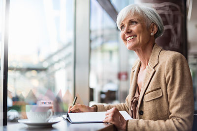 Smiling senior businesswoman taking notes in a cafe