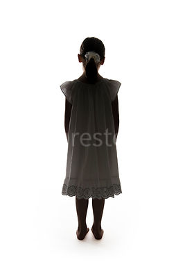 A barefoot little girl in a night dress, in silhouette – shot from mid level.