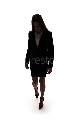 A woman, in silhouette, walking towards camera and looking down – shot from eye level.