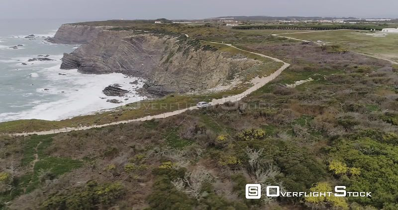 Aerial drone looking down at a small car driving on a dirt trail on the coastal cliffs of Portugal