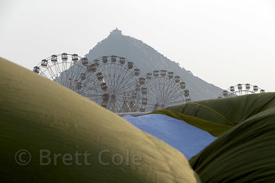 Savitri temple and ferris wheels are seen past the billows of several hot air balloons at the Pushkar Camel Fair, Pushkar, Ra...