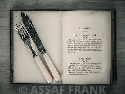 Old cookery book open with an old fork and knife