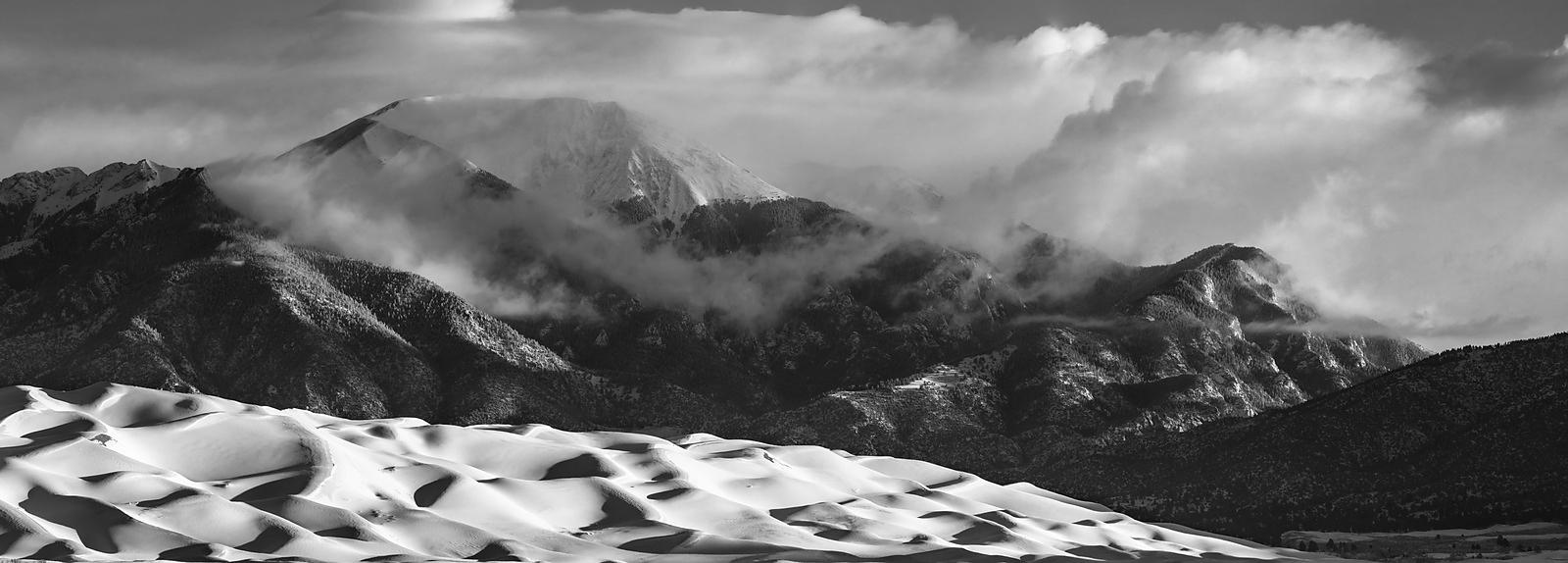 Dramatic light on a snowy dunefield.  Panorama.  Great Sand Dunes National Park.