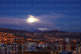 High rise buildings in Sopocachi, full moon behind clouds and Mt Illimani, La Paz, Bolivia