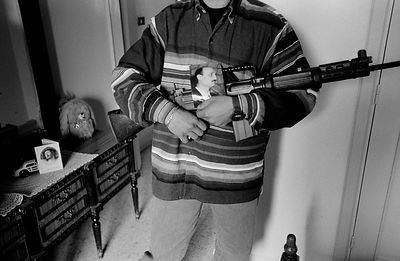 A young Maronite Christian man holds an Israeli assault rifle