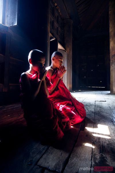 Two buddhist novice monks praying inside a monastery. Myanmar