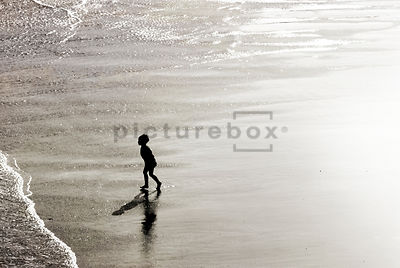 An atmospheric image of a child on a beach.