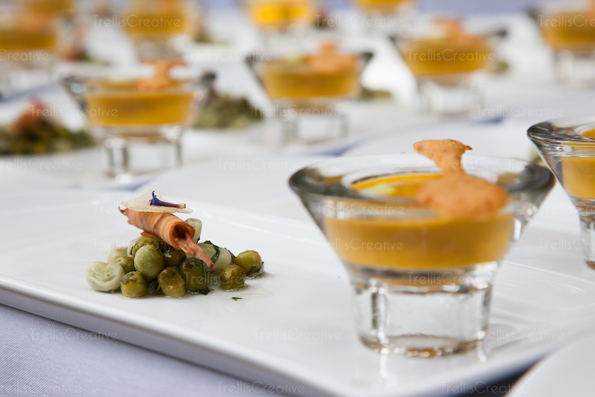 Small cups of soup with green peas lined up for service at an event