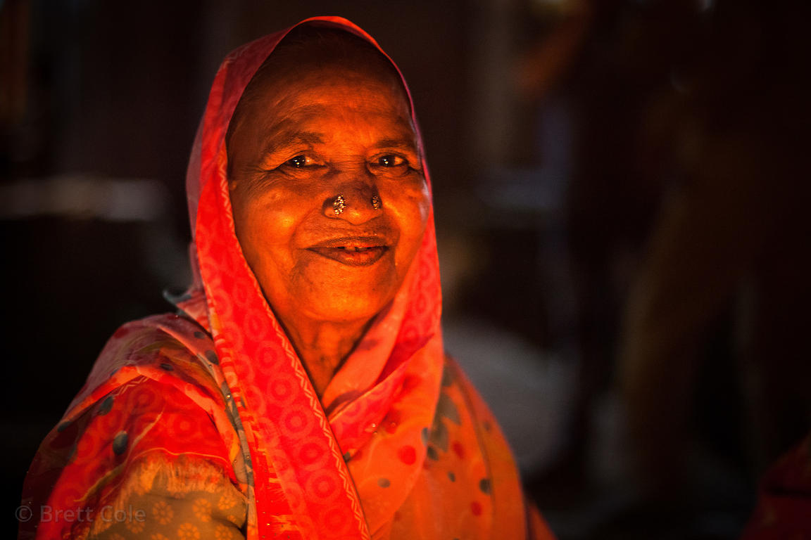 Nighttime portrait of an elderly women selling fish in the Kokri Agar slum, Mumbai, India.