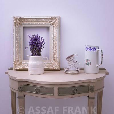 Flower vase with photoframe and tea set on table