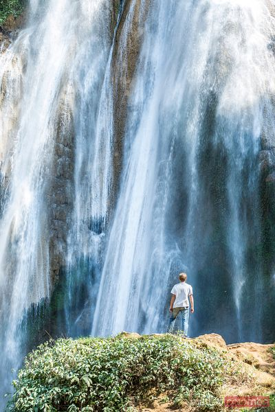 Adult man in front of waterfall