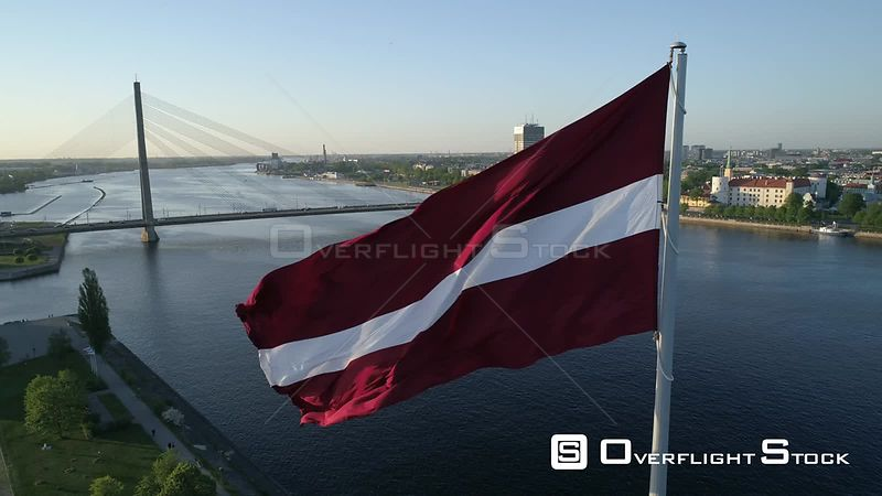 Aerial drone closeup shot of a large flag of Latvia with skyline of Riga in background