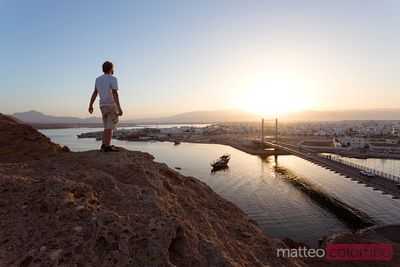 Man watching sunset over Sur harbour, Oman