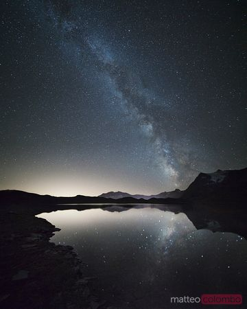 Milky way reflected in mountain lake, Piedmont, Italy