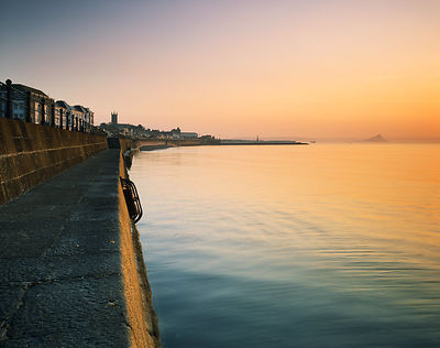 A calm and atmospheric sunrise at the Promenade in Penzance with the Jubilee Pool and St Michael's Mount in the distance.