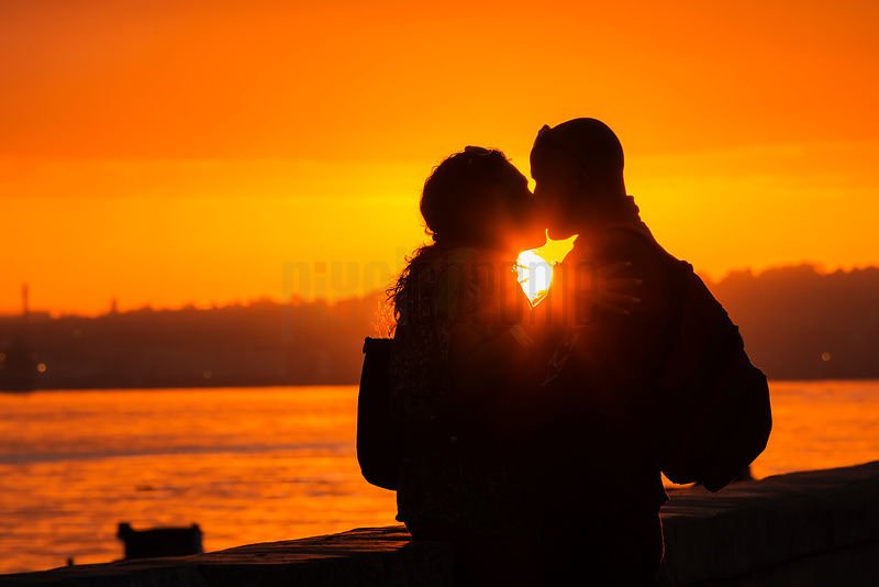 Silhouette of Lovers Kissing at Sunrise on the Harbour Wall