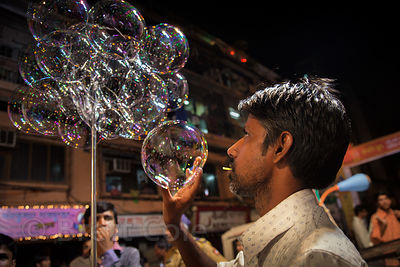 A bubble salesman blows bubbles during the Ganesh Chaturthi festival in Shekwalhi, Mumbai, India.
