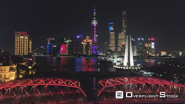 Illuminated Shanghai Downtown at Night. Lujiazui District and Huangpu River. China. Aerial View. Drone is Flying Upward. Esta...