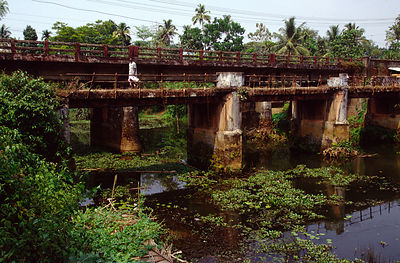 India - Kerala - A man walks accross a bridge over the backwaters