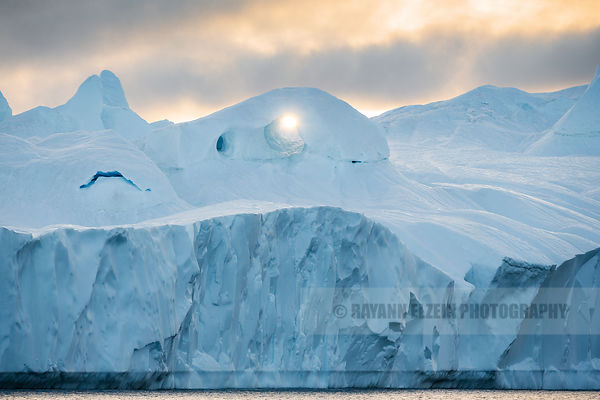 The sun shines through and arch in a large iceberg in Ilulissat, Greenland