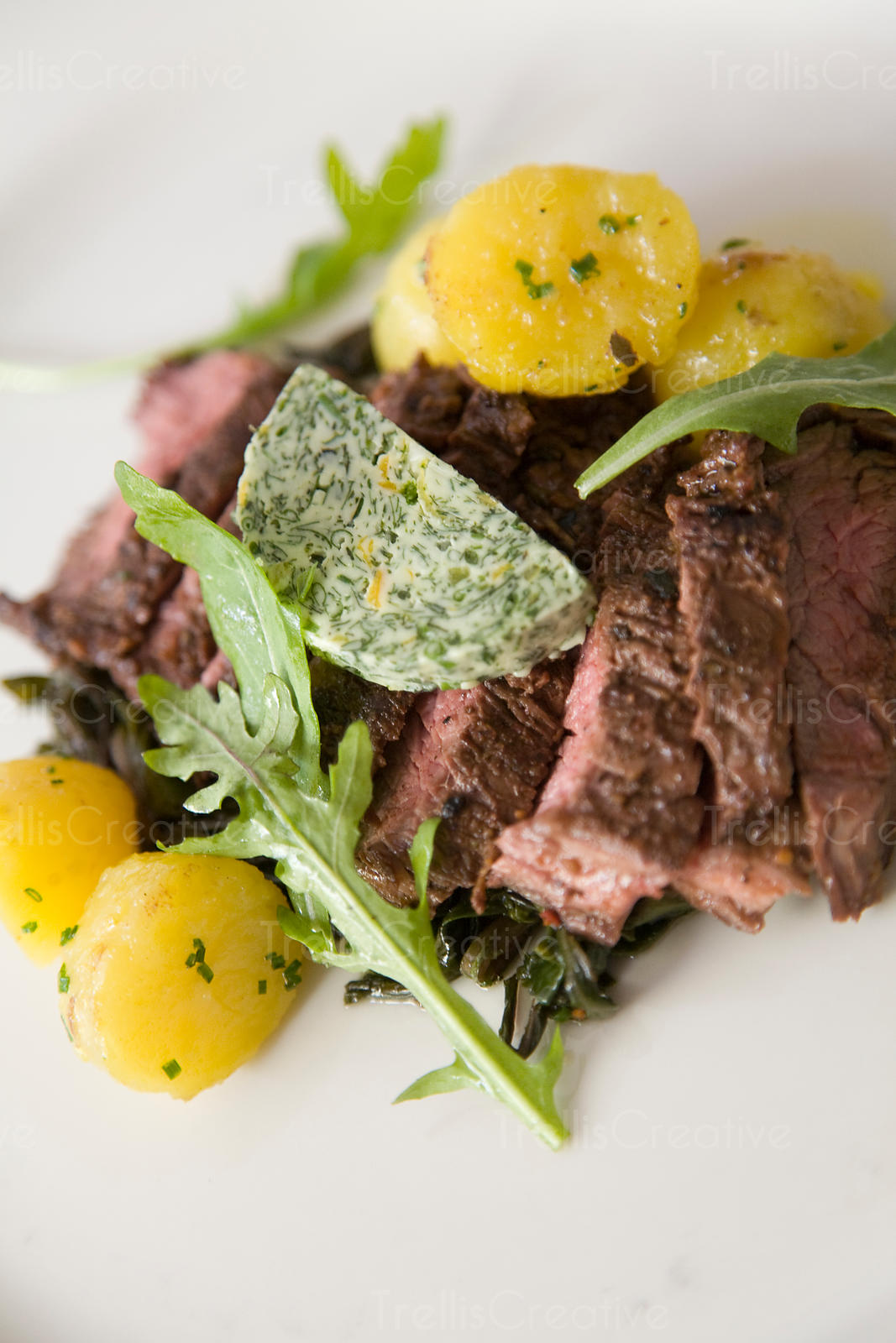 Beef flank steak served with potatoes and tarragon butter
