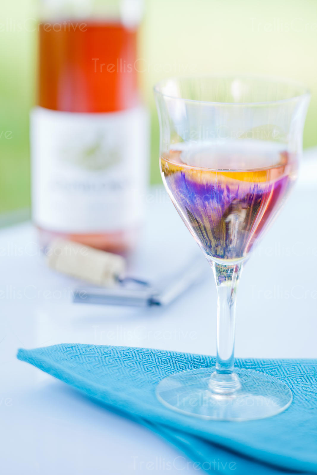An interesting shaped wine glass with an opened bottle of rose wine on an outdoor patio table