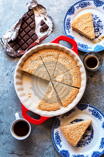 Sliced shortbread cookies in a pan with cup of coffee and a piece of chocolate on the table