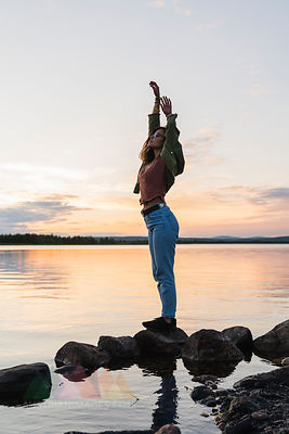 Finland, Lapland, woman standing at the lakeside at twilight