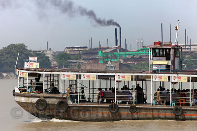 A ferry on the Hoogly River passes the Hanuman Jute Mill, belching out smoke, Kolkata, India.