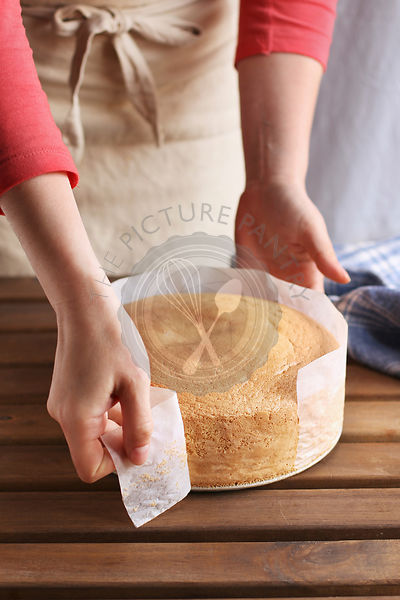 Female hands peeling the parchment paper from the sides of the sponge cake.