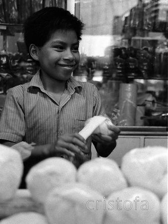 Small boy winding cheese to sell in the Merida market