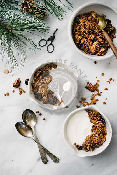 Bowls of yogurt and granola on a marble background.