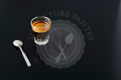 Close-up of a shot of espresso on black metal table