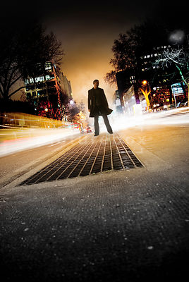An atmospheric image of a mystery man, standing on an island in a busy road in London.