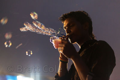 A man sells bubble makers on the beach at night, Juhu Beach, Mumbai, India.