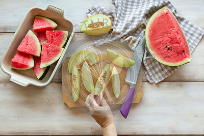 Slices of watermelon and green melon on the table