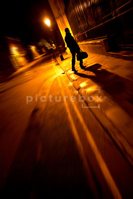 An atmospheric image of the silhouette of a mystery man, walking with a bag, in a dark street at night.